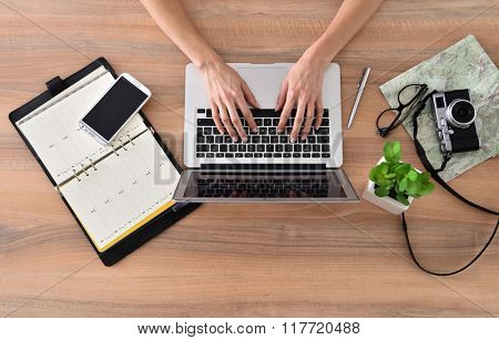 Upper view of woman's hands typing on laptop keyboard