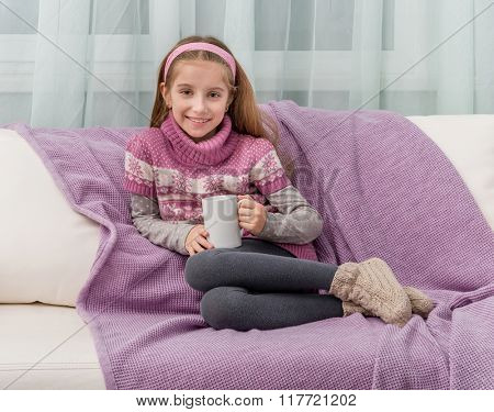 lovely little girl on a sofa with warm blanket holding a cup of tea