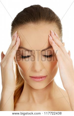 Woman with a headache holding head.