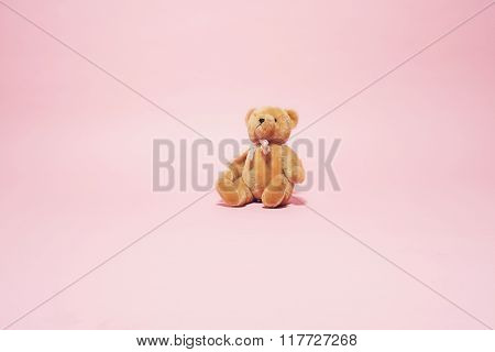 Vintage Brown Teddy Bear With Bow Against Pink Background.