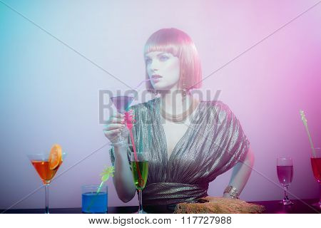 Glamorous Woman Sipping Cocktail In Smoky Bar
