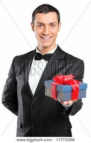 Smiling Man In Black Suit And Bow Tie Giving A Gift