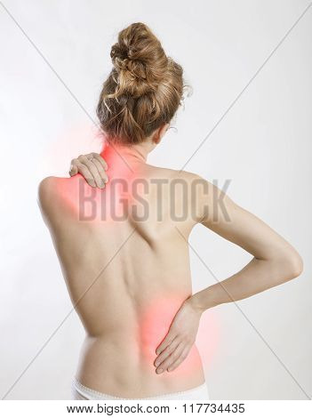 a young woman holds her back in pain white background and exempted