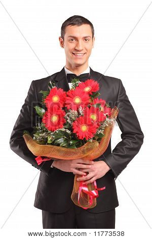 Handsome Male Wearing Black Suit And Bow Tie Holding A Bouquet Of Flowers