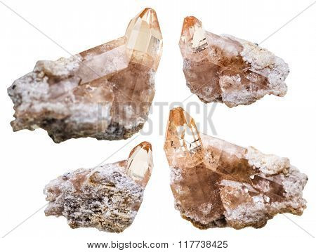 Four Topaz Crystals On Rocks Isolated On White