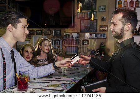 Man accompanied by two ladies paid the bill at the counter with a credit card