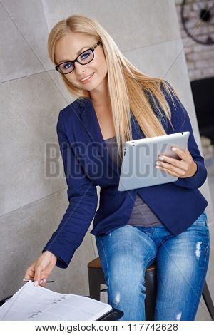 Happy young businesswoman working , using tablet and personal organizer, smiling, looking at camera.