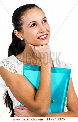 Smiling thoughtful woman holding plastic folder with fist on chin on white screen