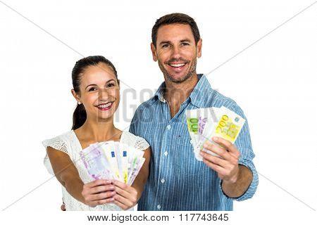 Confident couple holding money on white screen