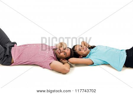 Smiling couple laying on floor with hands on their heads on white screen