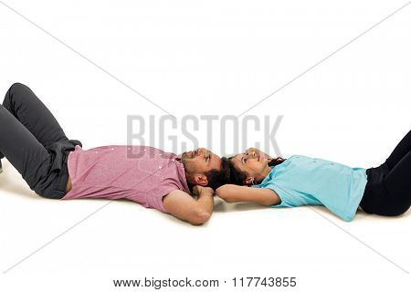 Peaceful young couple laying on floor with hands on their heads on white screen