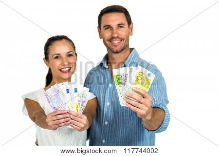 Portrait of couple holding money on white screen