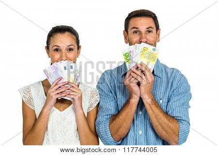 Excited couple holding money on white screen