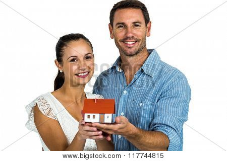 Smiling couple holding house model on white screen