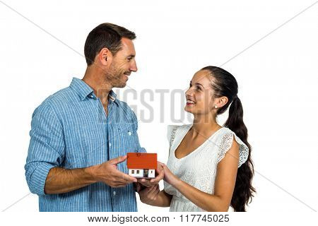 Face to face couple holding house model on white screen