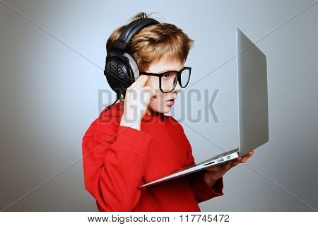 Cute boy in spectacles and headphones working on his computer. Studio shot.