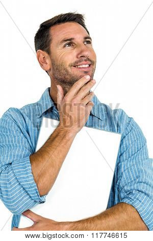 Thoughtful young man with hand on chin holding laptop on white screen