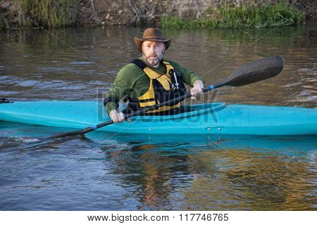 adult, male paddler, in a blue plastic whitewater kayak on a calm river