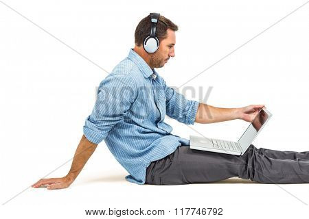 Man sitting on floor using laptop and headphones on white screen
