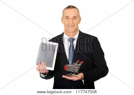 Portrait businessman with shopping cart and tablet