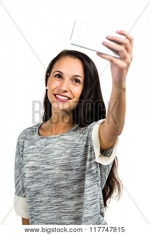 Smiling young woman taking selfie on white screen