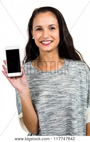 Smiling woman showing smartphone screen at camera on white screen