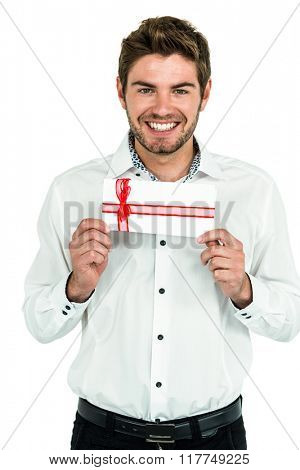 Handsome man holding gift box on white screen