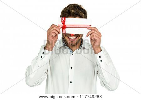 Handsome man covering eyes with gift box on white screen