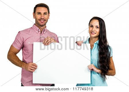 Smiling couple showing blank sheet on white screen