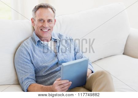 Happy man using tablet computer in the living room