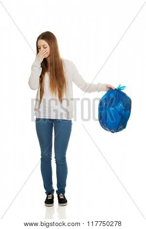 Young woman holding a full garbage bag.