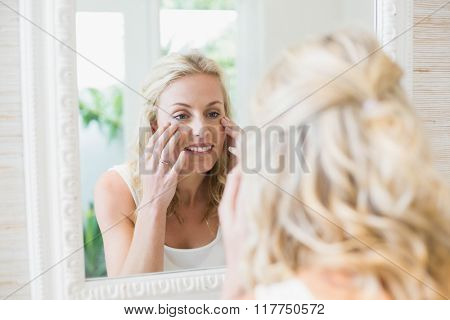 Beautiful woman looking at herself in the mirror in the bathroom