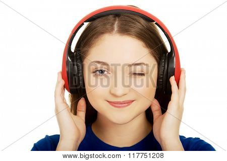 Woman with headphones blinks eye.