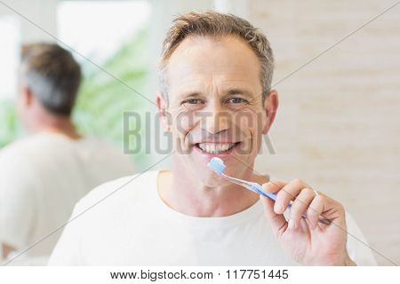 Handsome man brushing his teeth in the bathroom