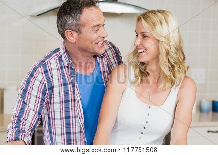 Cute couple looking at each other in the kitchen