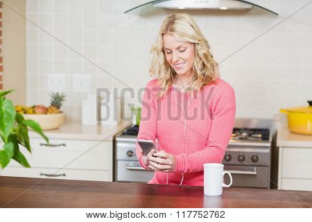 Beautiful woman listening to music in the kitchen