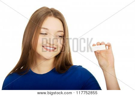 Happy teenager holding pregnancy test.