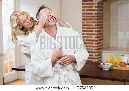 Woman covering her husband eyes in the kitchen