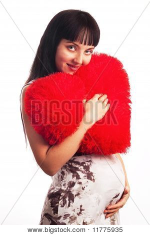 Beautiful, Young Pregnant Girl Hugging A Soft Big Heart. Mom, Mother, Motherhood, Waiting For The Ch