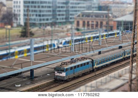Passenger train on tracks with in urban area with depth of field.
