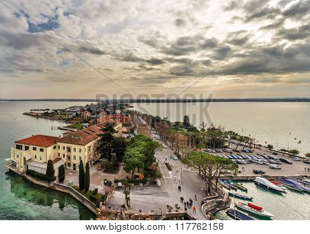 View Of Peninsular City Of Sirmione At Sunset In Cloudy Day