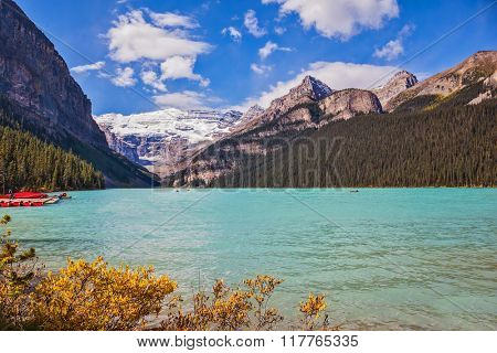 Lake Louise on a beautiful sunny day. The lake is surrounded by mountains, glaciers and pine forests