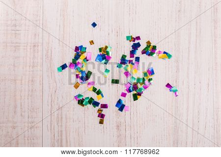 Colorful confetti on wood background