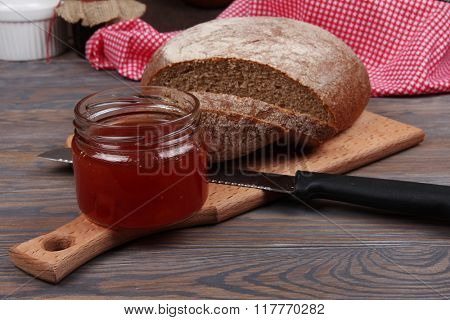 Rye bread and jam on wooden background