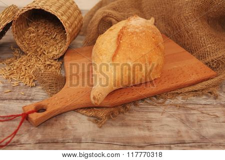 Homemade baked wheaten bread on wooden background with grains