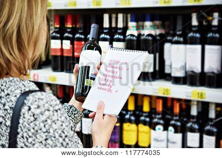 Girl Chooses Bottle Of Wine For Date In Store