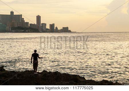 Boy Fishing At Malecon At Sunset