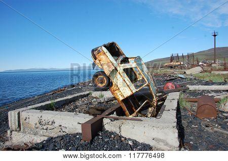 Old Broken Rusty Abandoned Car Upside Down At Sea Coast