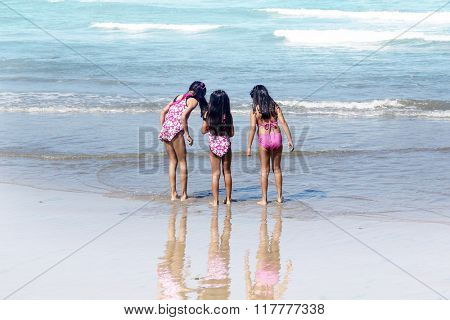Three little girls standing on the beach.