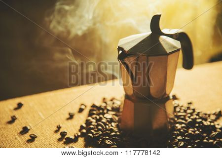 Artistic shot of old coffee maker and coffee beans, shot on canvas background